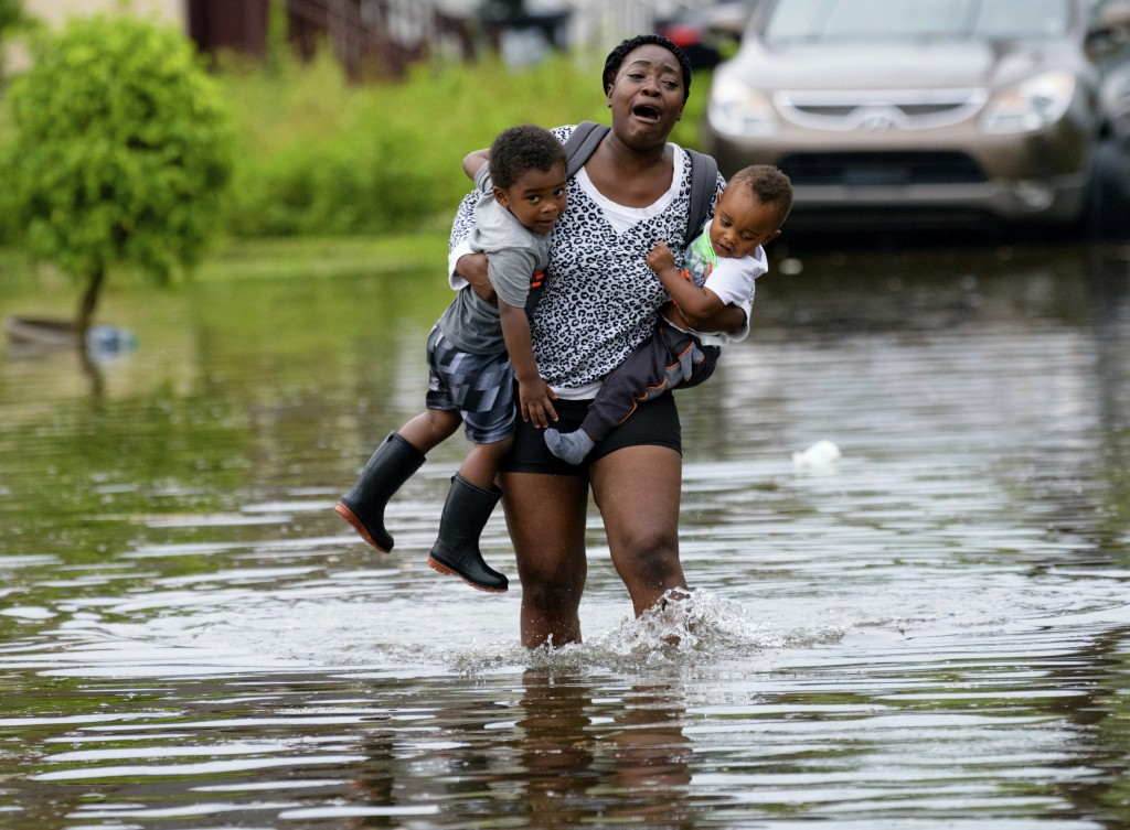 Terrian Jones reacts as she feels something moving in the water at her feet as she carries Drew and Chance Furlough to their mother on Belfast Street