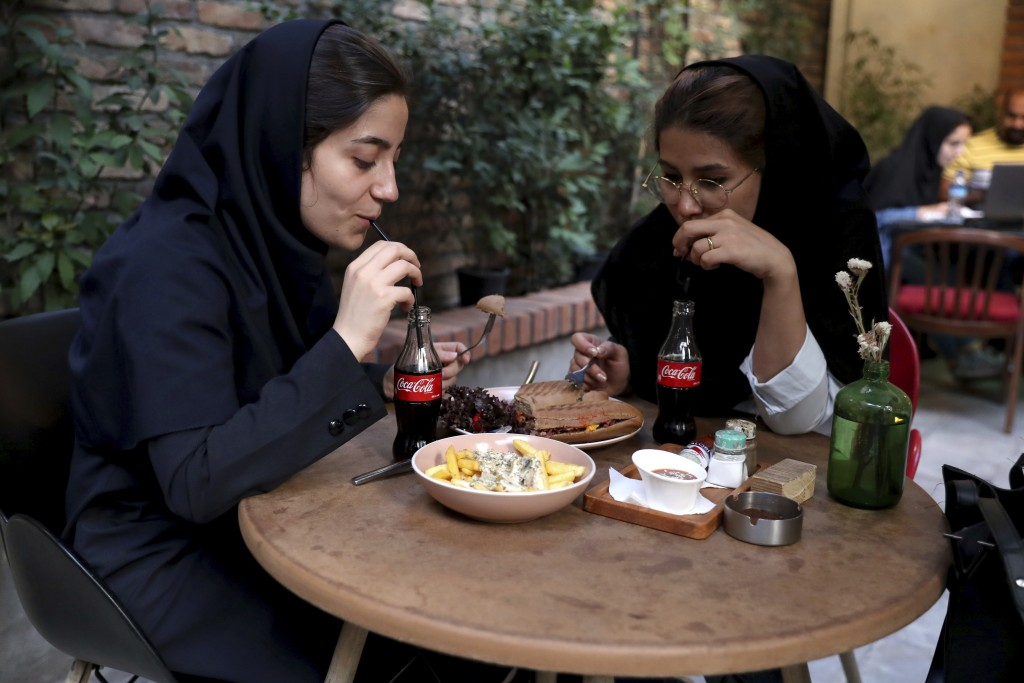 Two Iranians drink Coca-Cola at a cafe in downtown Tehran, Iran, Wednesday, July 10, 2019. Whether at upscale restaurants or corner stores, American b