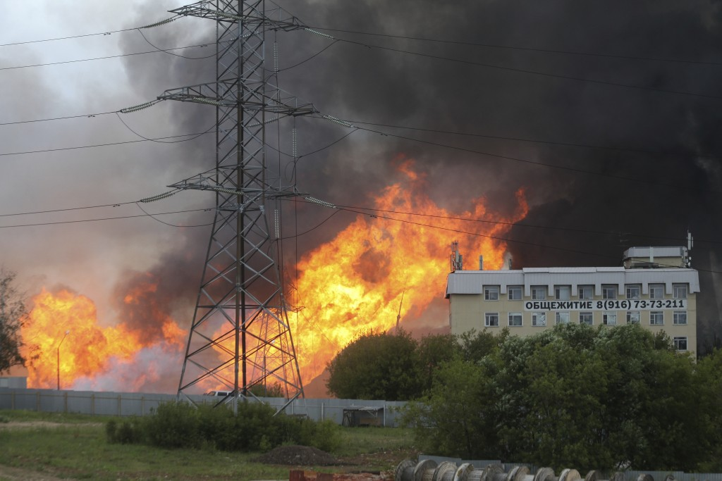 Black smoke and flames rise over a power station, in Mytishchi, outside Moscow, Russia, Thursday, July 11, 2019. The fire broke out on Thursday on the