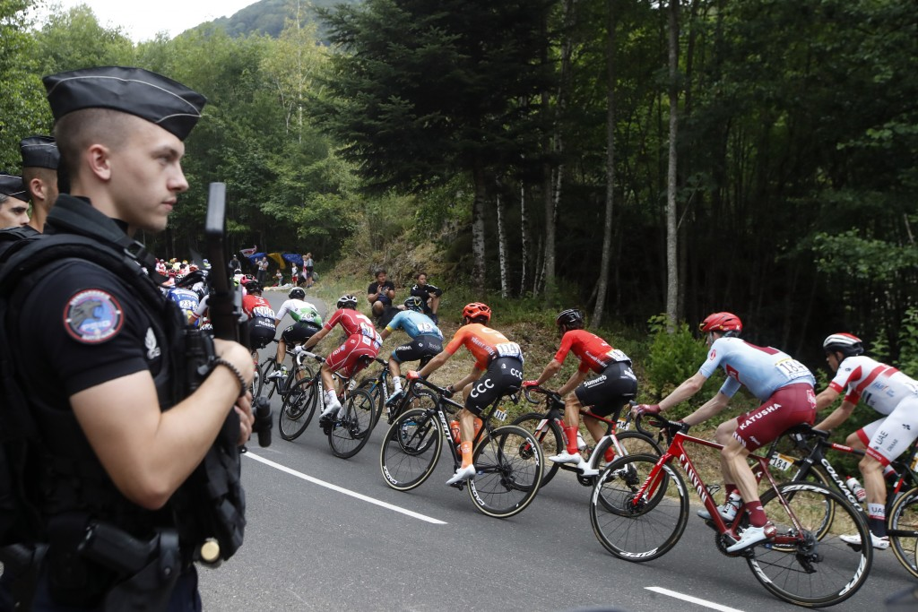 The pack rides past police officers during the sixth stage of the Tour de France cycling race over 160 kilometers (100 miles) with start in Mulhouse a...