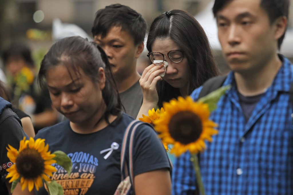 Attendees take part in a public memorial for Marco Leung, a 35-year-old man, who fell to his death weeks ago after hanging a protest banner against an...