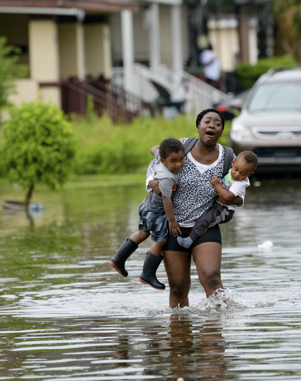 Terrian Jones reacts as she feels something moving in the water at her feet as she carries Drew and Chance Furlough to their mother on Belfast Street ...