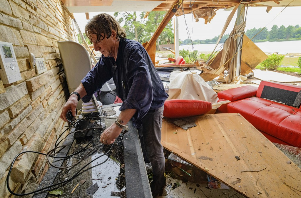 Eric Ehlenberger, a physician and neon artist, goes through his damaged home in New Orleans on Wednesday, July 10, 2019, following a storm that swampe