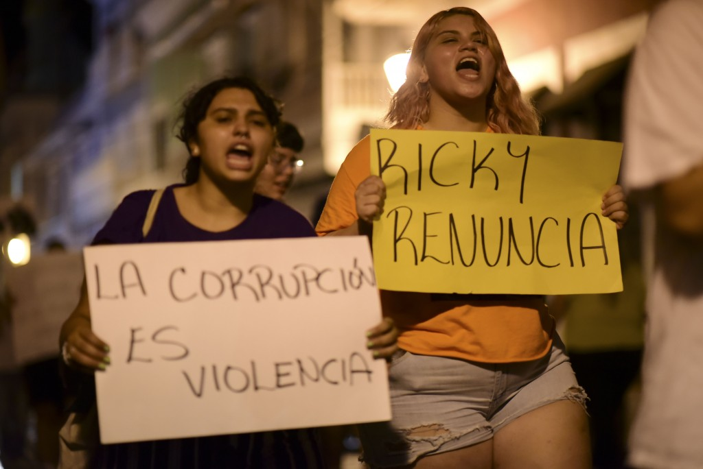 """Demonstrators holding signs that read in Spanish """"Corruption is violence"""" and """"Ricky renounce"""", protest near the executive mansion denouncing a wave o"""