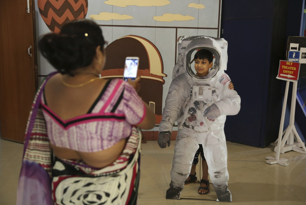 An Indian woman takes a photograph of her son as he poses in a cut-out of an astronaut at the Nehru Planetarium in New Delhi, India, Thursday, July 11