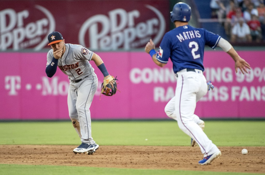 Houston Astros shortstop Alex Bregman (2) reacts after being hit in the face by a ground ball by Texas Rangers' Shin-Soo Choo as Jeff Mathis (2) runs ...