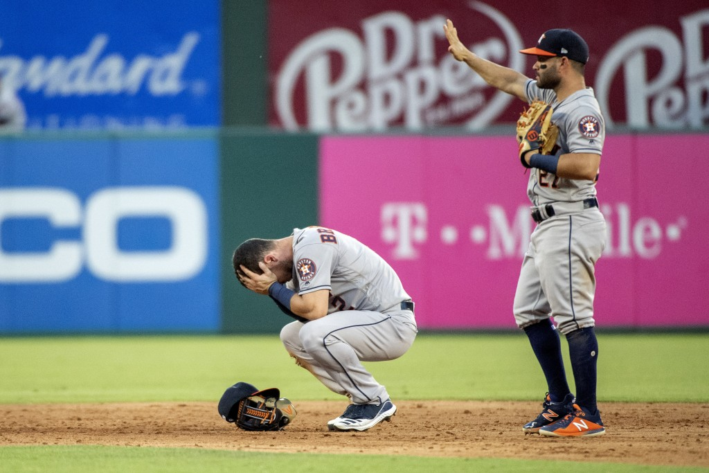 Houston Astros shortstop Alex Bregman reacts to being hit in the face by a ground ball by Texas Rangers' Shin-Soo Choo as second baseman Jose Altuve (