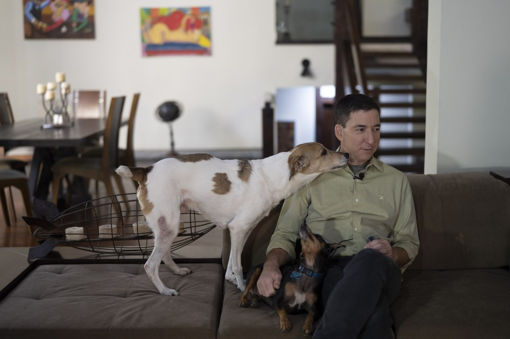 In this July 10, 2019 photo, U.S. journalist Glenn Greenwald, accompanied by his dogs Pulo, left, and Kane, sits during an interview at his home in Ri