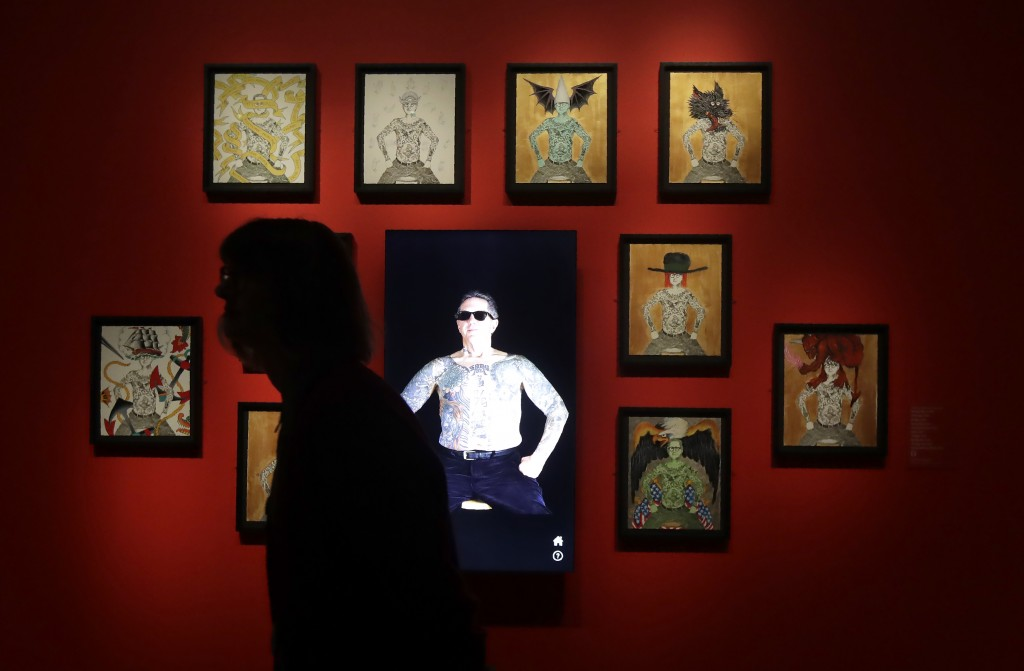 "In this Wednesday, July 10, 2019 photo, a woman walks past an interactive display of artwork and tattoos during a media preview of ""Ed Hardy: Deeper t"