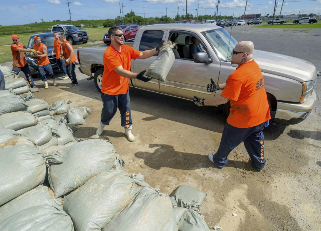St. Bernard Parish Sheriff's Office inmate workers move free sandbags for residents in Chalmette, La., Thursday, July 11, 2019 ahead of ahead of Tropi