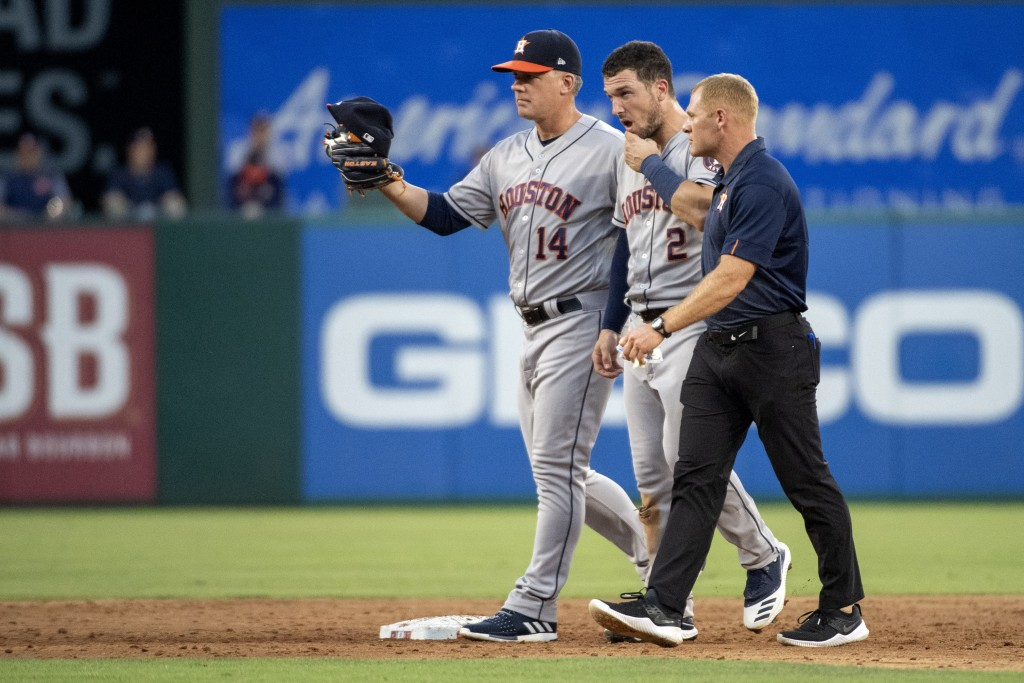 Houston Astros shortstop Alex Bregman (2) is escorted off the field by manager A. J. Hinch (14) and a trainer after taking a ground ball by Texas Rang...