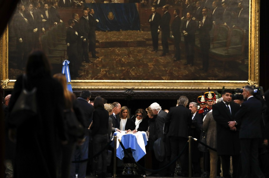 In this Tuesday, July 9, 2019 photo, relatives of former Argentine President Fernando De la Rua stand beside his coffin during his wake inside Congres