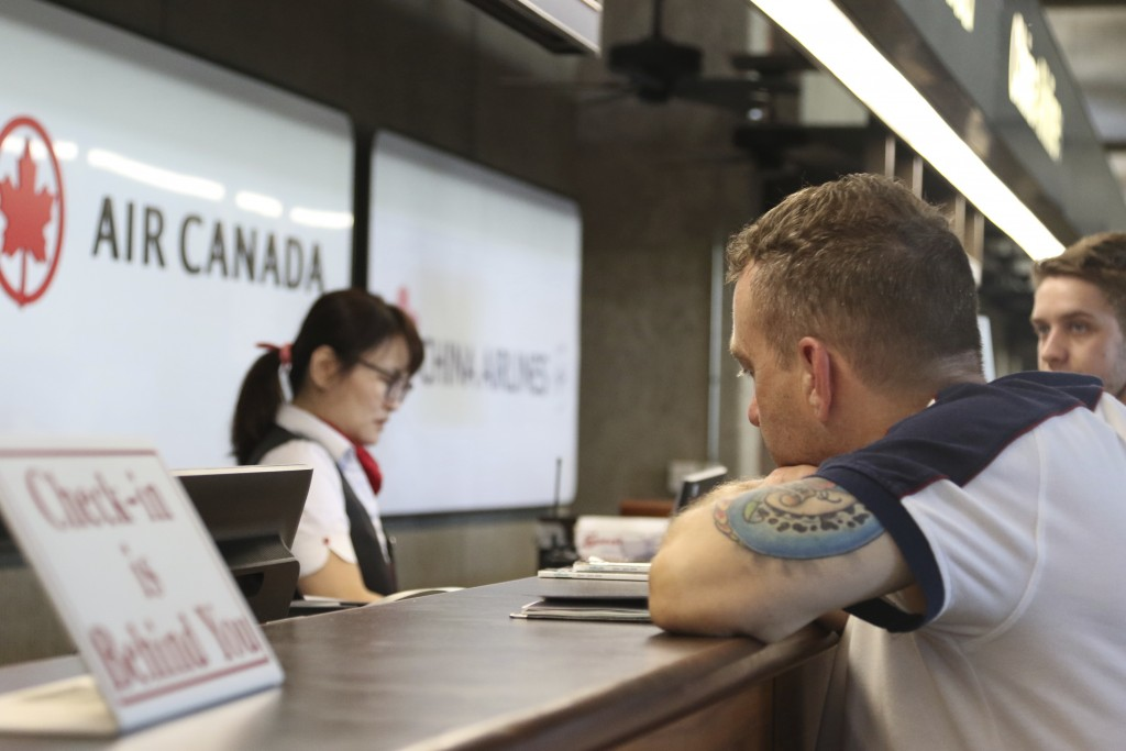 Andrew Szucs, right, who was on the Air Canada flight that made an emergency landing, waits for assistance at the Air Canada desk, Thursday, July 11,