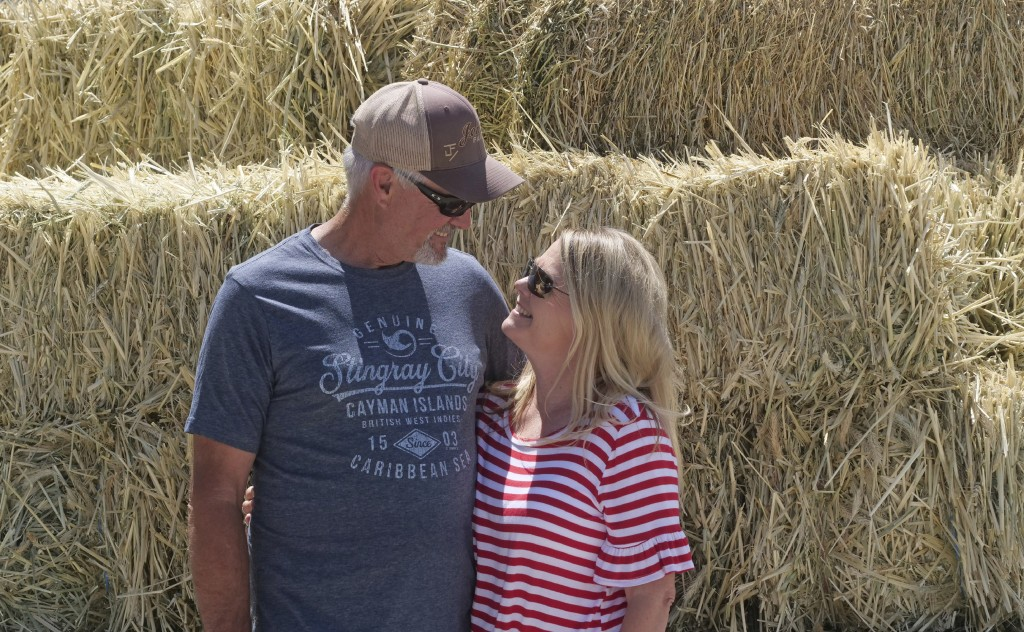 In this Wednesday, June 26, 2019, photo, Russell and Diane Jones stand in in front of alfalfa at their farm, in Nephi, Utah. The Joneses are fourth-ge