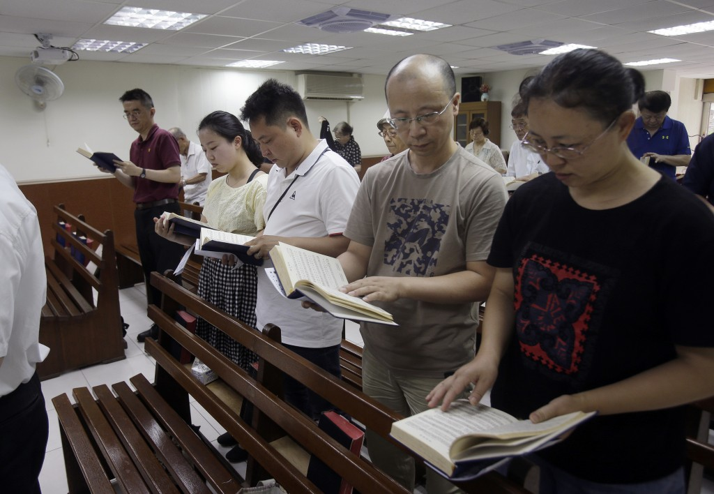 In this Sunday, July 7, 2019, file photo, from right; Ren Dejun, Liao Qiang, Peng Ran and Ren Ruiting follow a hymn book during service at a church in