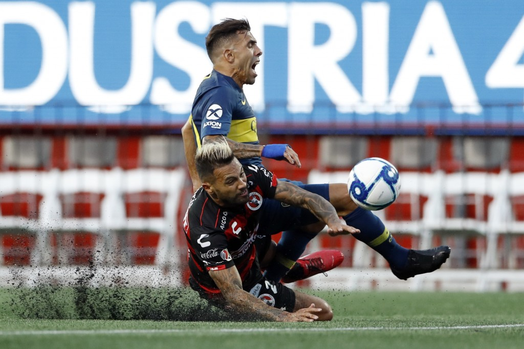 In this Wednesday, July 10, 2019 photo, Tijuana's Julian Velazquez, below, collides with Boca Juniors's Carlos Tevez during the first half of a friend