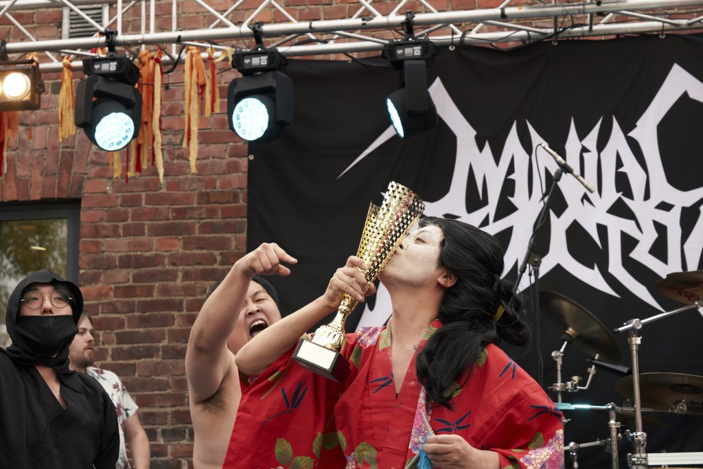 The Japanese team Giga Body Metal react with the trophy after being crowned Heavy Metal Knitting world champions with a show featuring crazy sumo wres