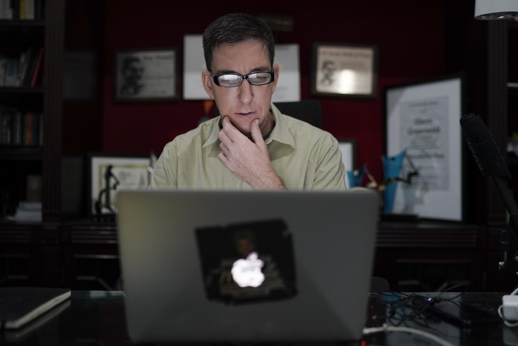 In this July 10, 2019 photo, U.S. journalist Glenn Greenwald checks his news website at his home in Rio de Janeiro, Brazil. Greenwald, an attorney-tur