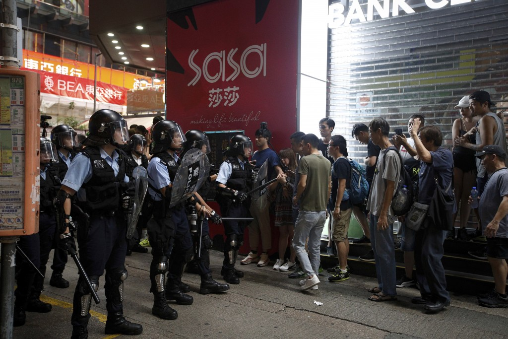 In this July 7, 2019, photo, riot police prevent p...