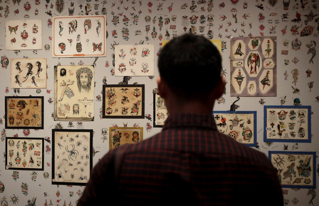 """In this Wednesday, July 10, 2019 photo, a man looks at a wall of tattoos during a media preview of """"Ed Hardy: Deeper than Skin"""" at the de Young Museum..."""