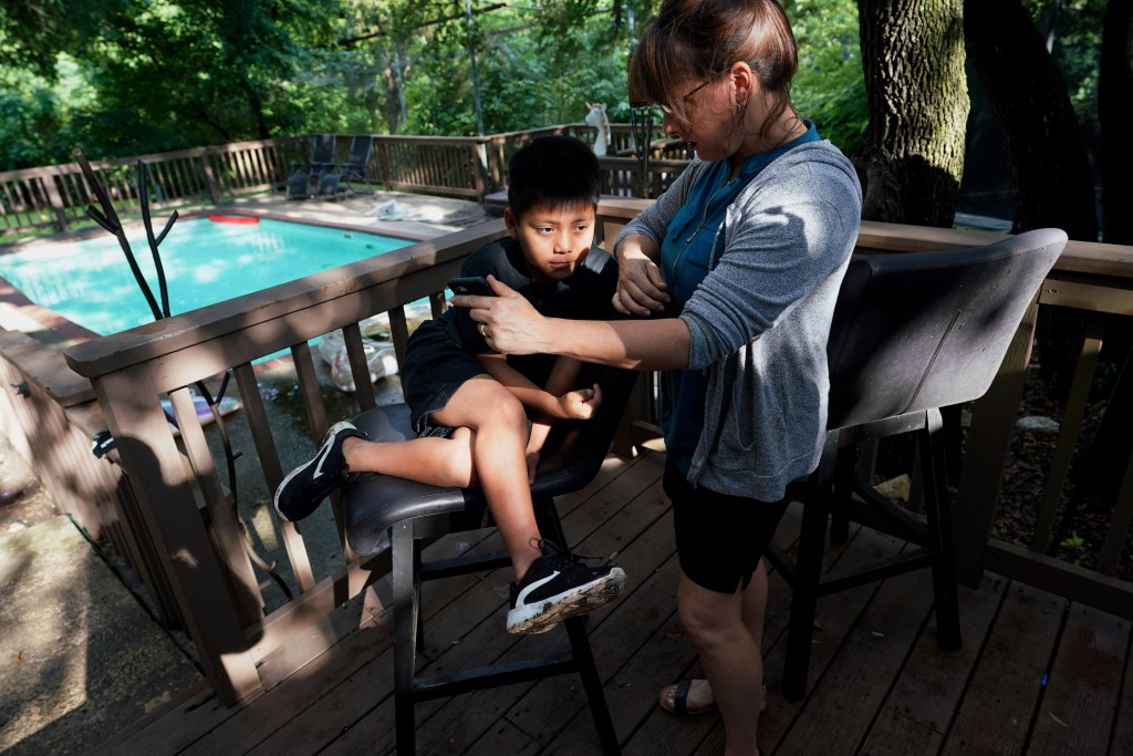 Holly Sewell helps Byron Xol, 9, an immigrant from Guatemala, talk to his family by phone Monday, June 24, 2019, in Buda, Texas. Fourteen months earli