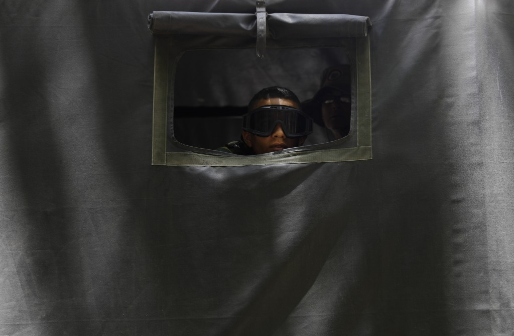 In this Friday, July 5, 2019 photo, a soldier wearing goggles looks through a window on a military truck during a parade marking Independence Day in C