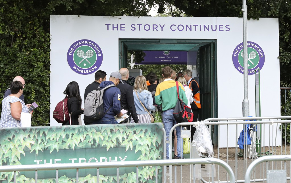 In this Tuesday, July 9, 2019 tennis fans wait in line for tickets to enter the Wimbledon Tennis Championships in London. For many the Wimbledon exper