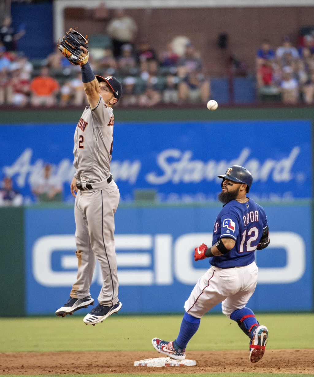 Houston Astros shortstop Alex Bregman (2) misses the relay throw as Texas Rangers' Rougned Odor (12) cruises into second with a double during the thir...