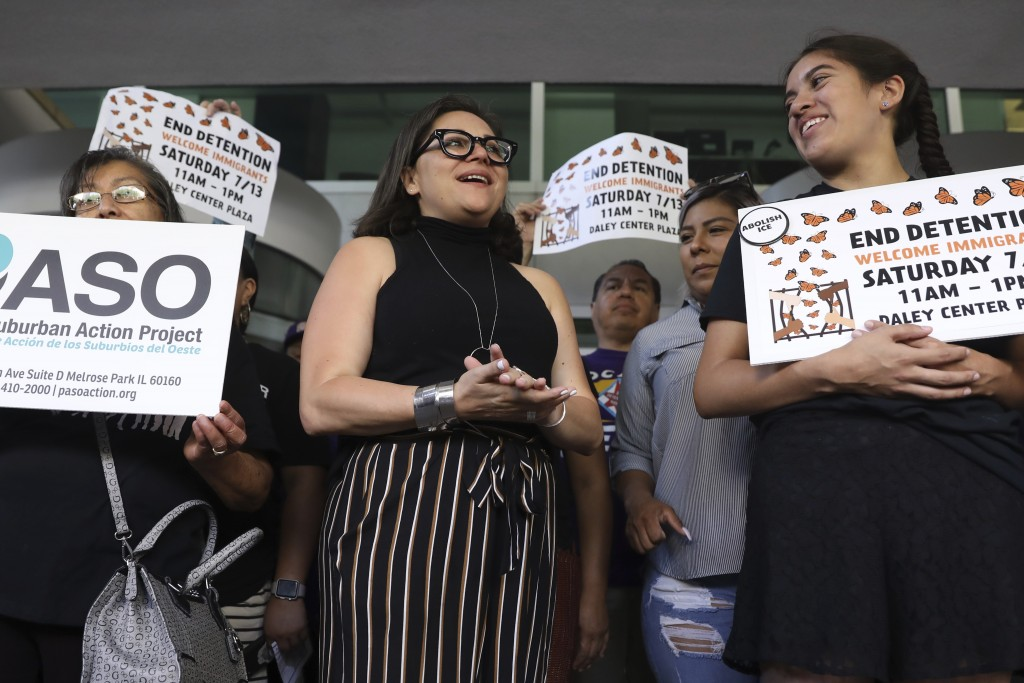 Mony Ruiz-Velasco, center, director of PASO West Suburban Action Project, chants with demonstrators following a new conference outside the U.S. Citize