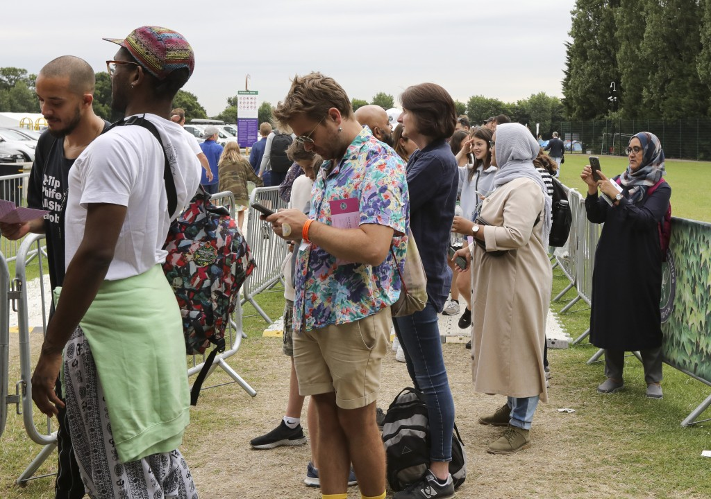 In this Tuesday, July 9, 2019, tennis fans wait in a queue to get tickets to enter the Wimbledon Tennis Championships in London. For many the Wimbledo