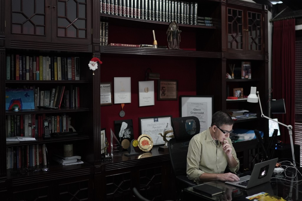 In this July 10, 2019 photo, U.S. journalist Glenn Greenwald checks his news website, at his home in Rio de Janeiro, Brazil. Being the center of contr