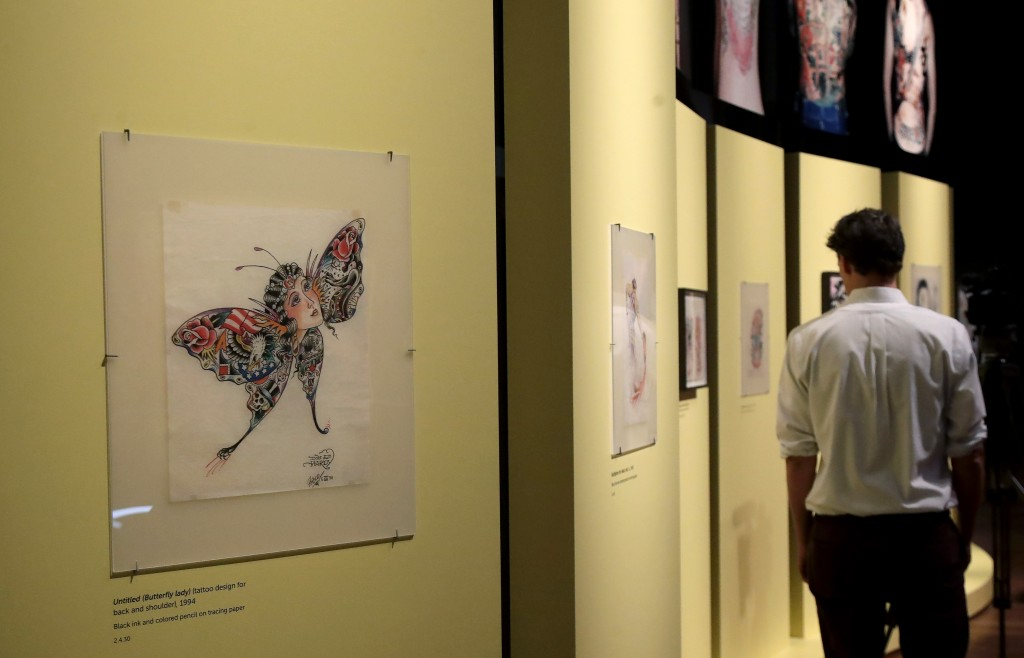 "In this Wednesday, July 10, 2019 photo, a man walks near artwork created by Ed Hardy during a media preview of ""Ed Hardy: Deeper than Skin"" at the de"
