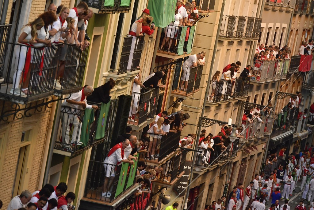 Revellers wait for the start of the running of the during the running of the bulls at the San Fermin Festival, in Pamplona, northern Spain, Friday, Ju