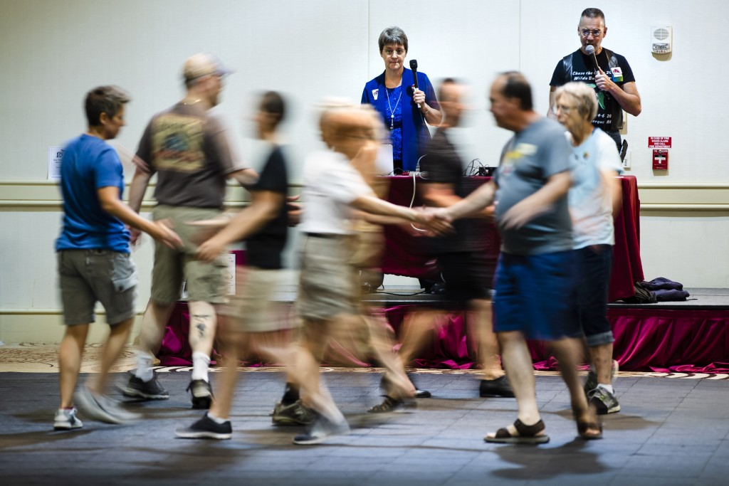 This July 3, 2019 photo shows Marge Coahran, left, of Toronto, and Scott Amspoker Albuquerque, N.M., calling to dancers during the annual Internationa