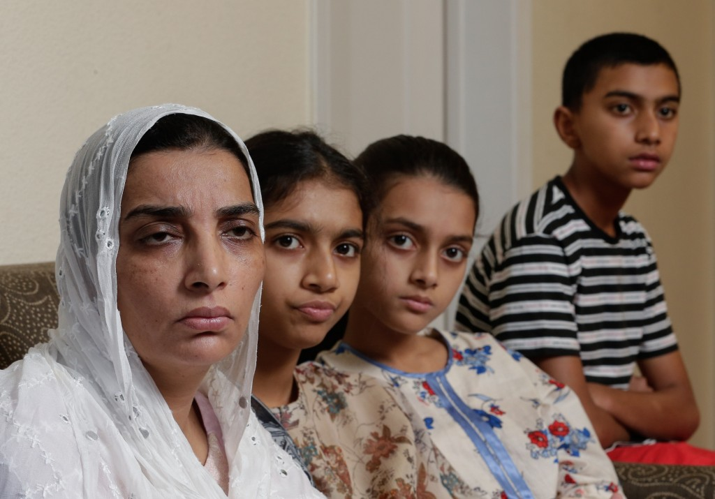 In this Wednesday July 10, 2019 photo, family members of Santa Fe High School shooting victim Sabika Aziz Sheikh, 17, pose in their home during an int