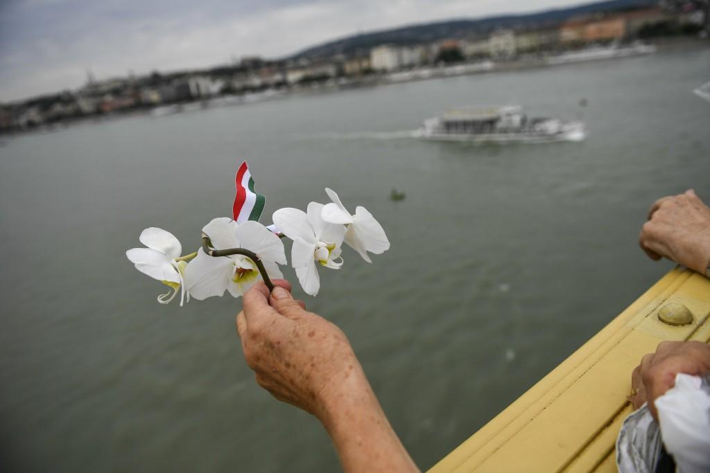 A mourner holds orchids on Margaret Bridge across ...