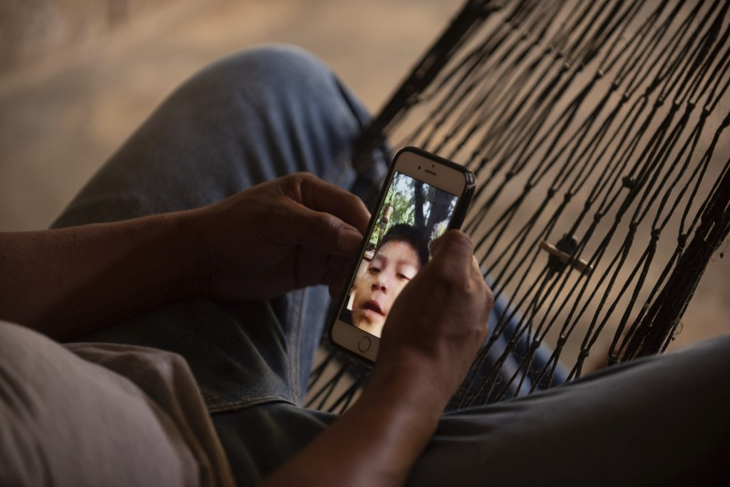 David Xol, talks with his son, Byron, over a video call from his home in San Miguel El Limon, 475 kilometers (295 miles) away from Guatemala City, Sun
