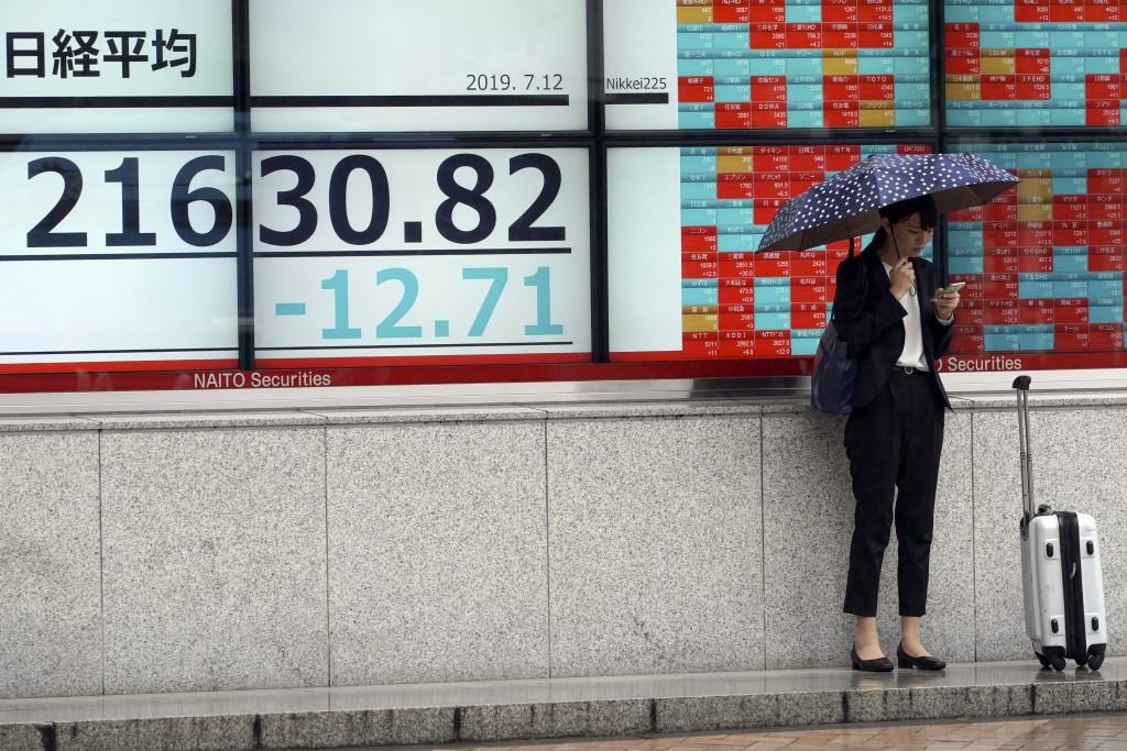A woman stands near an electronic stock board showing Japan's Nikkei 225 index at a securities firm in Tokyo Friday, July 12, 2019. Shares in Asia are...