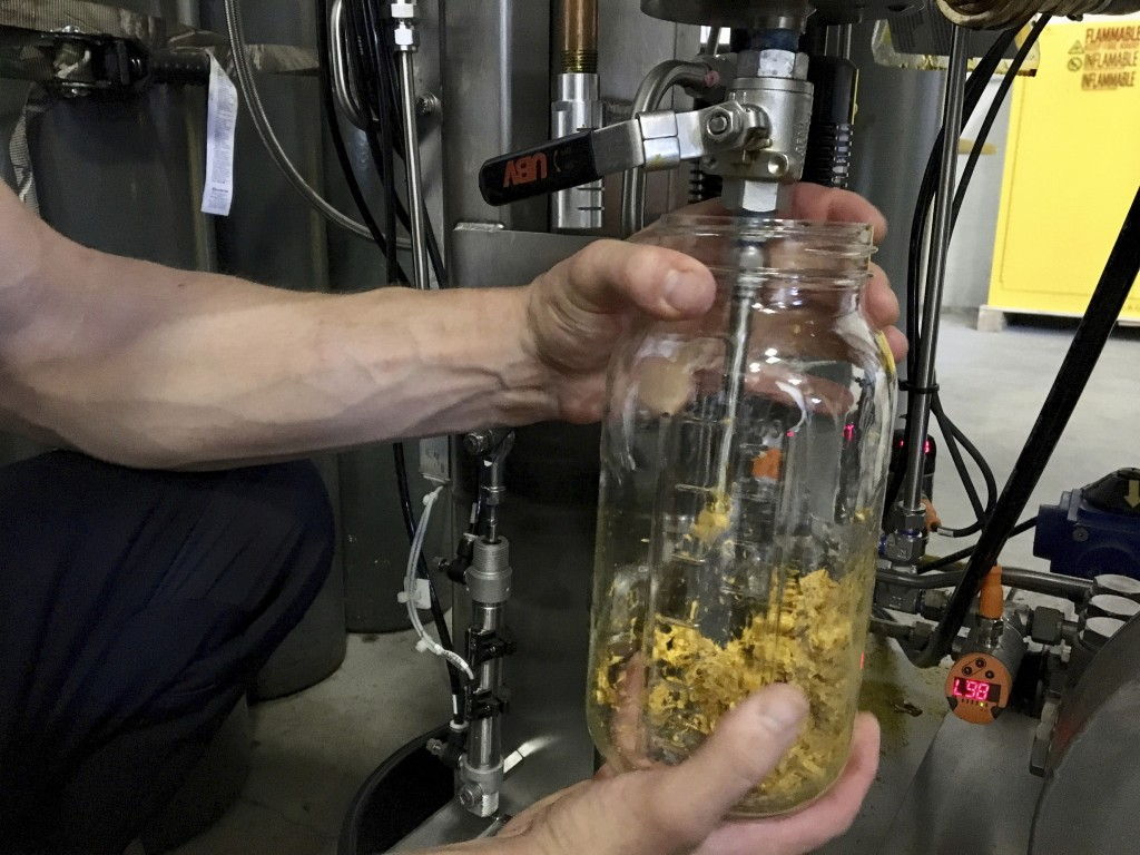 In this Tuesday, July 2, 2019 photo, Brent Steffensen, a hemp extractor at the processing facility Wasatch Extraction, uses a machine to extract fats,