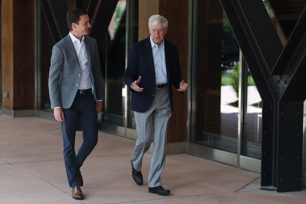 FILE - In this June 29, 2019, file photo, Charles Koch, chief executive officer of Koch Industries, right, talks with Brian Hooks, a network leader fo...