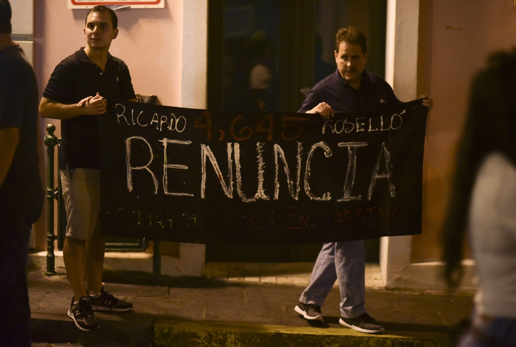 """Citizens carrying a banner that reads in Spanish """"Ricarod Rosello, renounce"""" protest near the executive mansion denouncing a wave of arrests for corru"""