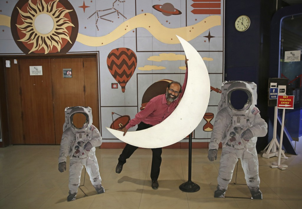 An employee playfully hugs a cut-out of a crescent moon at the Nehru Planetarium in New Delhi, India, Thursday, July 11, 2019. India is looking to tak