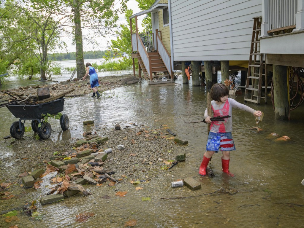 Delilah Campbell, 4, right, and her sister, Tallulah Campbell, 8, clear driftwood and other debris in preparation of Tropical Storm Barry near New Orl...