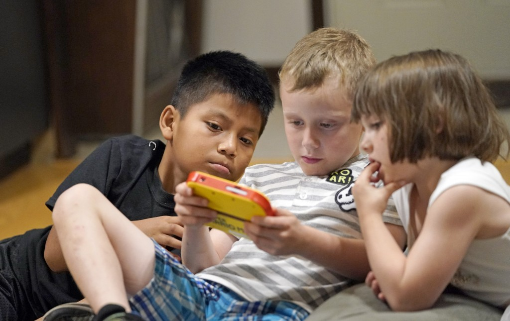 Byron Xol, 9, left, an immigrant from Guatemala, and Windy Sewell, right, watch her brother, Desmond Sewell, play an electronic game Monday, June 24, ...