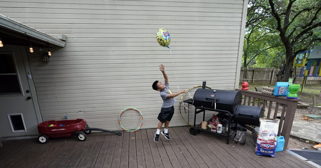Byron Xol, an immigrant from Guatemala, plays with a balloon before his birthday party Sunday, June 23, 2019, in Buda, Texas. Byron, now staying with ...
