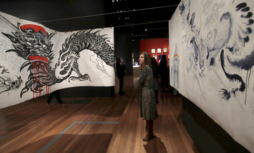 In this Wednesday, July 10, 2019 photo, a woman looks at a 2,000-square-foot scroll suspended from the ceiling on which Ed Hardy painted 2,000 dragons