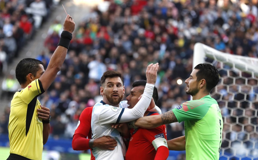 In this Saturday, July 6, 2019 photo, Argentina's Lionel Messi, center left, and Chile's Gary Medel, center right, scuffle as referee Mario Diaz, from