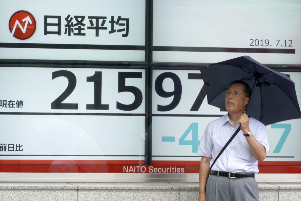 A man stands by an electronic stock board showing Japan's Nikkei 225 index at a securities firm in Tokyo Friday, July 12, 2019. Shares in Asia are mos