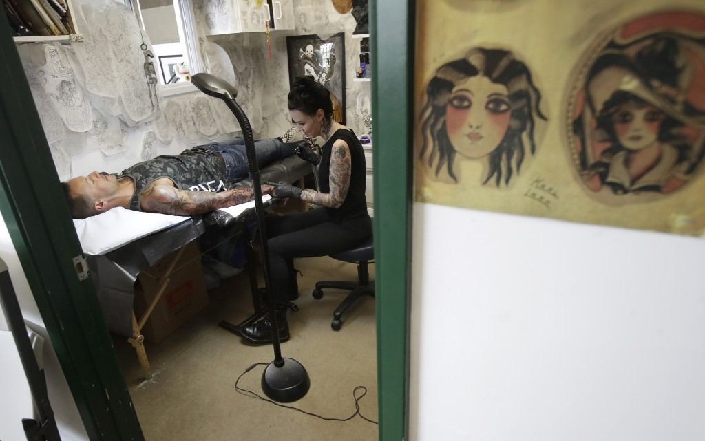 In this June 26, 2019, photo Mary Joy Scott works on the outline of a tattoo for Nick Chavira at Ed Hardy's Tattoo City in San Francisco. Hardy may be...