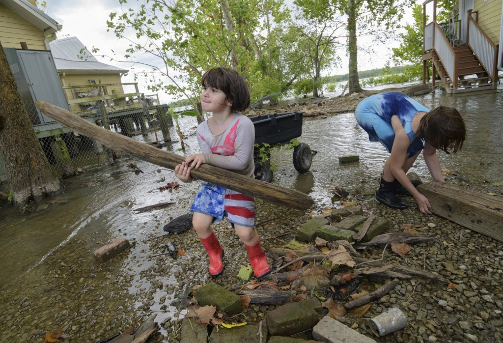 Delilah Campbell, 4, left, and her sister, Tallulah Campbell, 8, clear out driftwood and other debris in preparation of Tropical Storm Barry near New